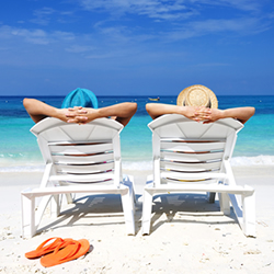 retired couple relaxing on beach chaires