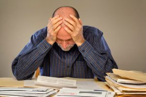 frustrated man with files and paperwork