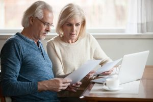 concerned couple reviewing papers in front of computer